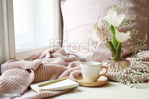 Cozy Easter, spring still life scene. Cup of coffee, opened notebook, pink knitted plaid on windowsill. Vintage feminine styled photo, floral composition with tulips, hyacinth and Gypsophila flowers.
