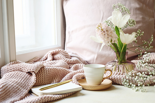 Cozy Easter, spring still life scene. Cup of coffee, opened notebook, pink knitted plaid on windowsill. Vintage feminine styled photo. Floral composition with tulips, hyacinth and Gypsophila flowers.