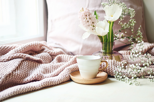 Cozy Easter, spring still life scene. Cup of coffee, pink knitted plaid and floral bouquet in vase on windowsill. Vintage feminine styled photo. Composition with tulips, hyacinth and Gypsophila flowers