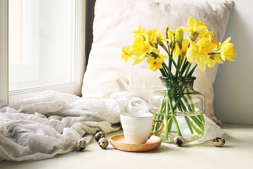 Cozy Easter, spring still life scene. Cup of coffee, wooden plate, quail eggs and vase of flowers on windowsill. Floral composition with yellow daffodils, narcissus. Vintage feminine styled photo.