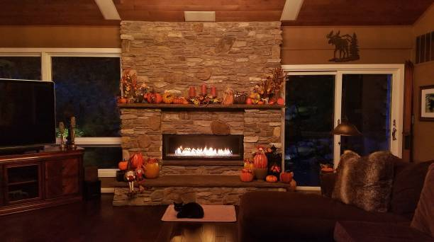 Cozy Family Room, Rustic Decor, with Large Stone Fireplace Glowing in the Evening stock photo
