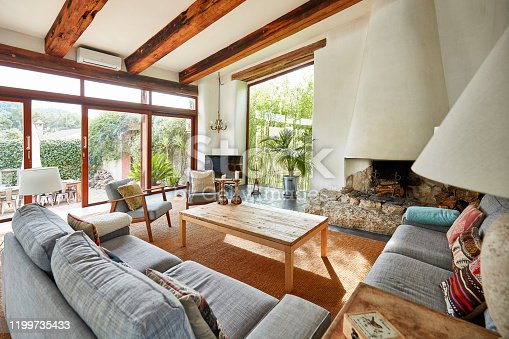 View of a spacious living room with fireplace in a bright Mediterranean farmhouse.