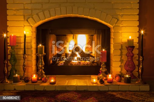istock Cozy fireplace setting with candles (P) 504680421