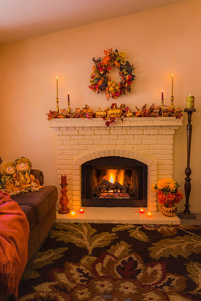cozy fireplace with fall decorations and candles (p) - herbst girlande stock-fotos und bilder