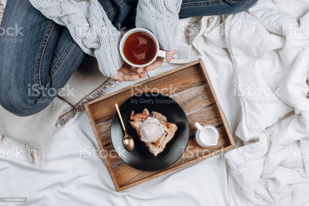 Cozy flatlay of bed with wooden tray with pie, ice cream and black tea and woman's hands in grey sweater holding cup