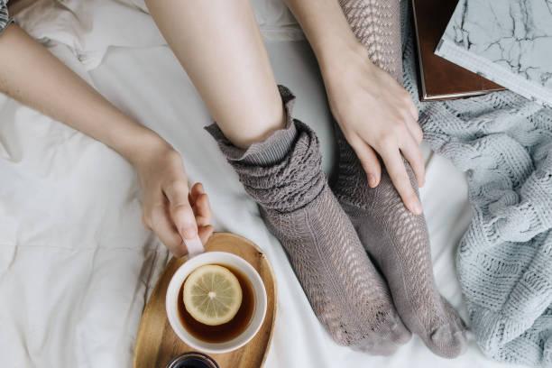 cozy flatlay of woman's legs in warm grey stockings in bed with knitted sweater and books holding cup of lemon tea, selective focus - herbata ziołowa zdjęcia i obrazy z banku zdjęć
