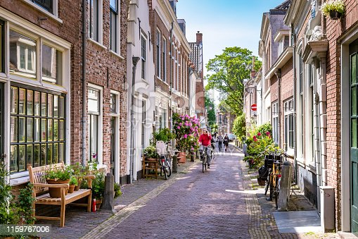 Haarlem, The Netherlands - May 31, 2019: Charming little green street in the city center of Haarlem with male cyclist and his phone and pedestrians