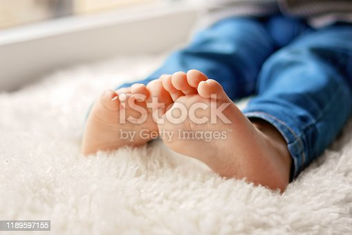 Cozy holidays at home. Close up photo of little child barefooted feet sitting on white furry blanket at window. Winter season lifestyle. Leisure time. Sweet childhood. Copy space
