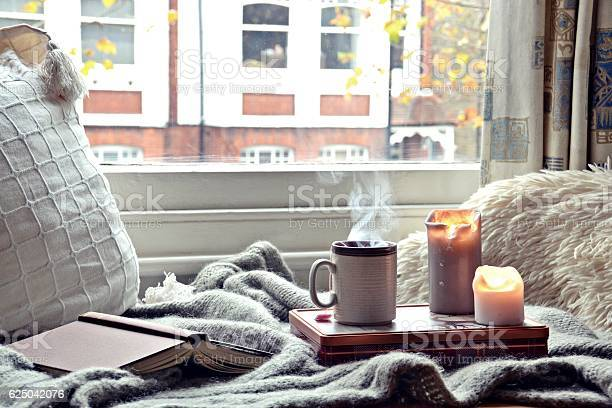 Cozy home. Candles, book and cup of tea