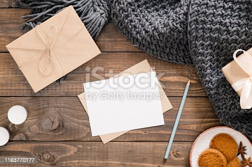 Cozy home desk, hygge, autumn fall concept. Blank paper card mockup, craft envelope, cookies, candles, women fashion scarf, gift box on wooden background. Flat lat, top view, copy space.