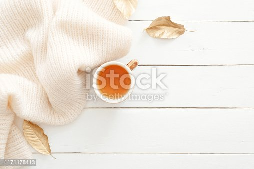 istock Cozy home desk table with knitted plaid, tea cup, fall leaves on wooden white background. Top view, flat lay, copy space. Autumn composition. Nordic hygge style concept. 1171178413