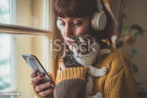 Woman at home listening to music and cuddle her cat