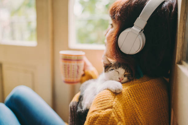 Cozy home Woman at home listening to music and drinking coffee headphones stock pictures, royalty-free photos & images