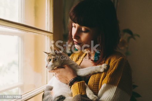 Young woman with cat staring through the window