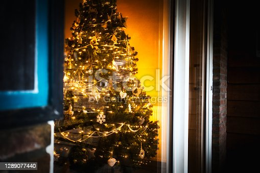 istock Cozy Home with Christmas tree near the window with sparkling glitter Christmas lights and decoration, cheerful an beautiful modern home interior 1289077440
