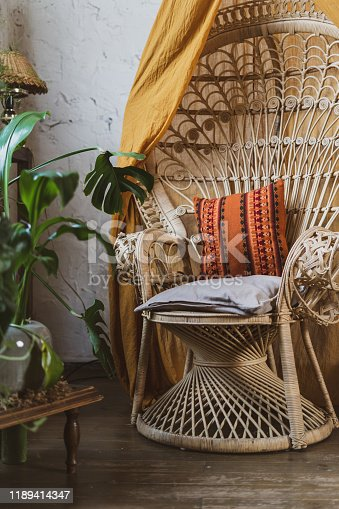 Vertical photo of wicker chair with pillows, cushions, green plants in flower pot at beautiful cozy room with boho style interior