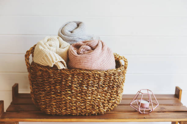 cozy interior details, scandinavian mininalistic lifestyle. Organizing clothes in wicker backets, seasonal wardrobe and house cleaning, ideas for winter season. stock photo