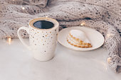 istock Cozy knitwear and a cup of coffee with a cake on white marble windowsill against white window background. Copy space. 1126374992