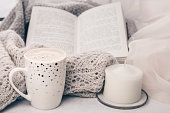 istock Cozy knitwear and a cup of coffee with a cake on white marble windowsill against white window background. Copy space. 1127952583