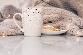 istock Cozy knitwear and a cup of coffee with a cake on white marble windowsill against white window background. Copy space. 1128008989