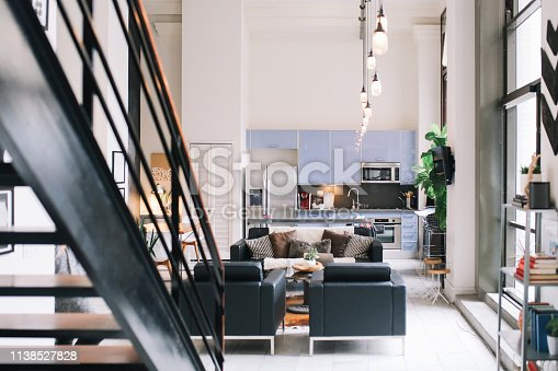 Interior of a large and bright loft apartment in Downtown Los Angeles, California. Living room with sofa and a worktable, with kitchen in the back.