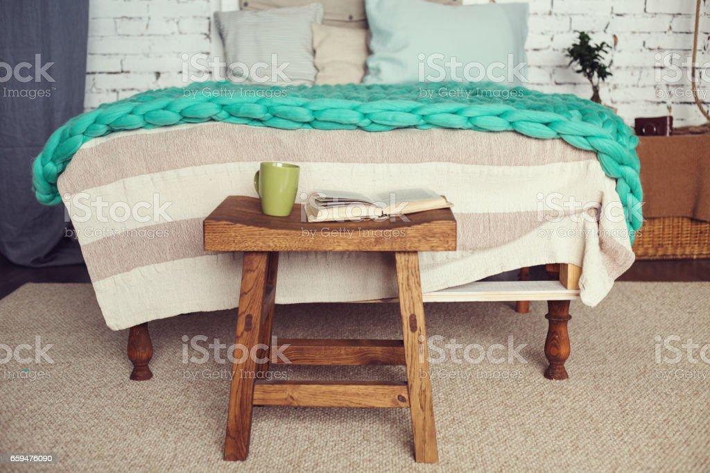Cozy loft interior of bedroom in pastel colors, wooden stool with cup and book, merino wool blanket on bed. stock photo