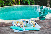 Cozy organic breakfast on plaid for two near private pool. Vintage style, all natural and homemade: muesli, jam, bread, yogurt, scrambled eggs, fresh coffee and fruits
