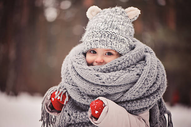 cozy outdoor portrait of happy toddler child girl in winter dreamy cozy outdoor portrait of toddler child girl in winter, wearing red gloves, grey knitted hat and scarf warm clothing stock pictures, royalty-free photos & images