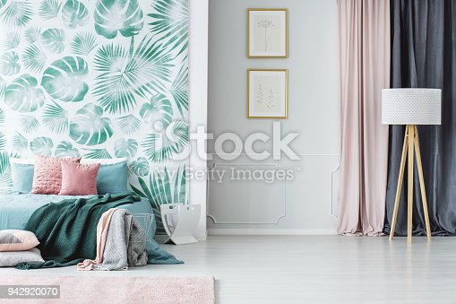 Wooden tripod floor lamp and a big bed with pillows and blankets in a cozy pale green and pink bedroom interior