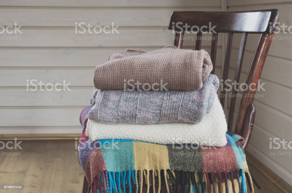 Cozy pile of warm clothes, sweaters on a vintage wooden chair. stock photo