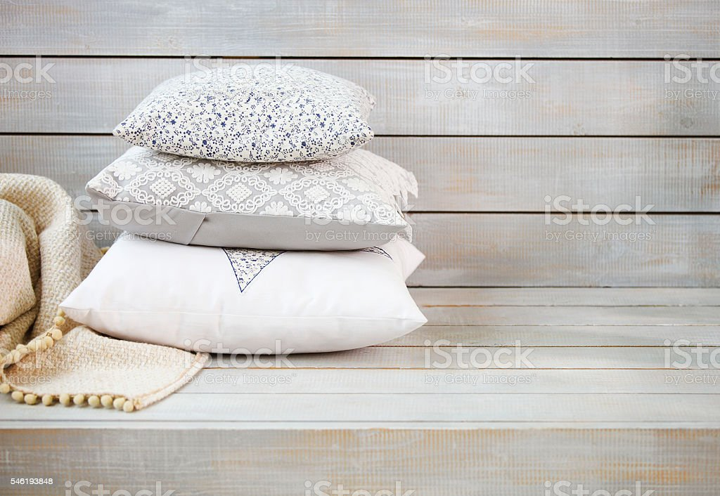 Cozy pillows and plaid on the light wooden background stock photo