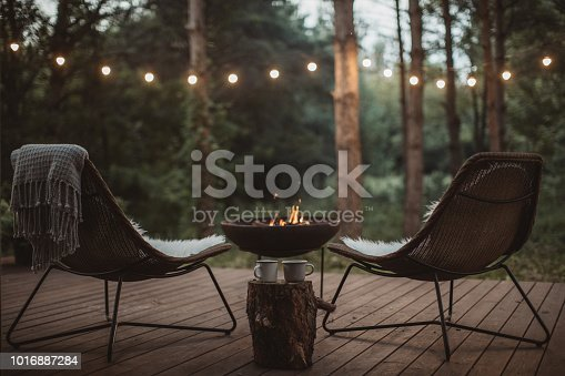 Cottage porch with two cozy chairs on it and fireplace. Blankets and coffee cups waiting for someone to enjoy in them.