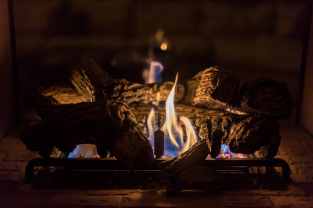 Cozy romantic gas fireplace at night Closeup of gas log fireplace on romantic evening log stock pictures, royalty-free photos & images