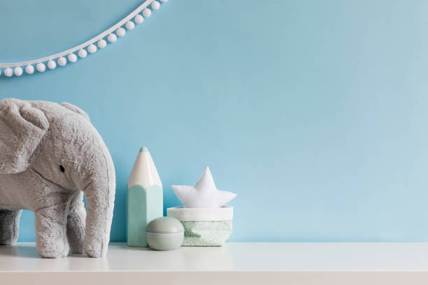 Cozy scandinavian newborn baby room with gray plush elephant ,white stars lamp and children accessories. Stylish interior with blue walls and haniging white garland. Template. Copy space. stock photo