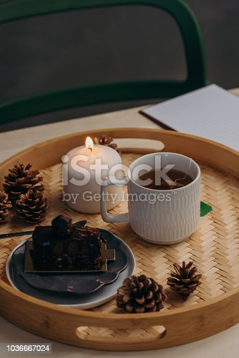 Cozy setting with green tea and chocolate vegan cake on table Autumn feeling of still life of hot drink with candle light