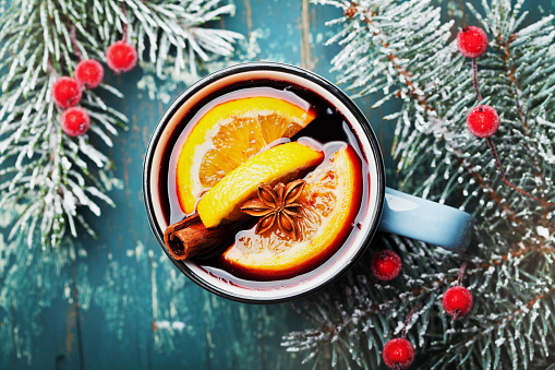 Cozy shot of christmas mulled wine or gluhwein with spices and orange slices on wooden teal table top view.