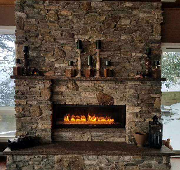 Cozy, Stone Fireplace With Flames Aglow in Winter stock photo