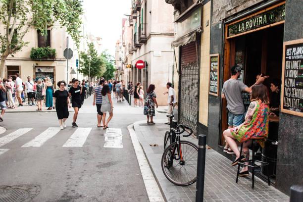 Acogedora calle en Barcelona, con bar, bicicleta y chica sentado al aire libre en una silla cerca de la cafetería y relajante personas en día de verano. Barcelona es una de las ciudades más famosas y divertidas de Europa - foto de stock