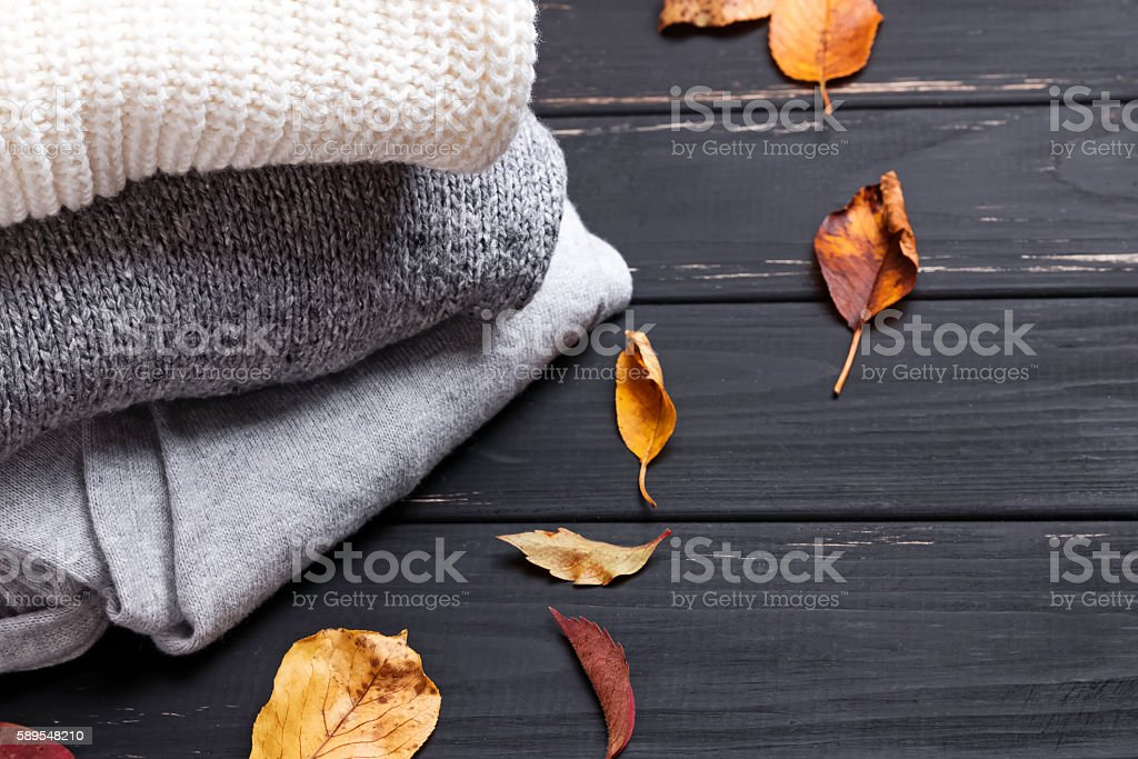 Cozy sweaters and autumn leaves stock photo