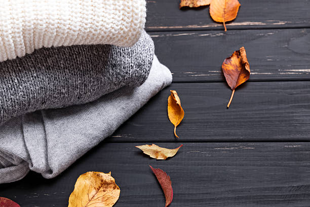 Cozy sweaters and autumn leaves - foto stock