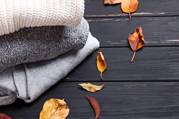 cozy sweaters and autumn leaves - moda de invierno fotografías e imágenes de stock