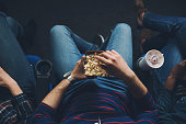 Unrecognizable young man watching the movie and eating popcorn in the cinema
