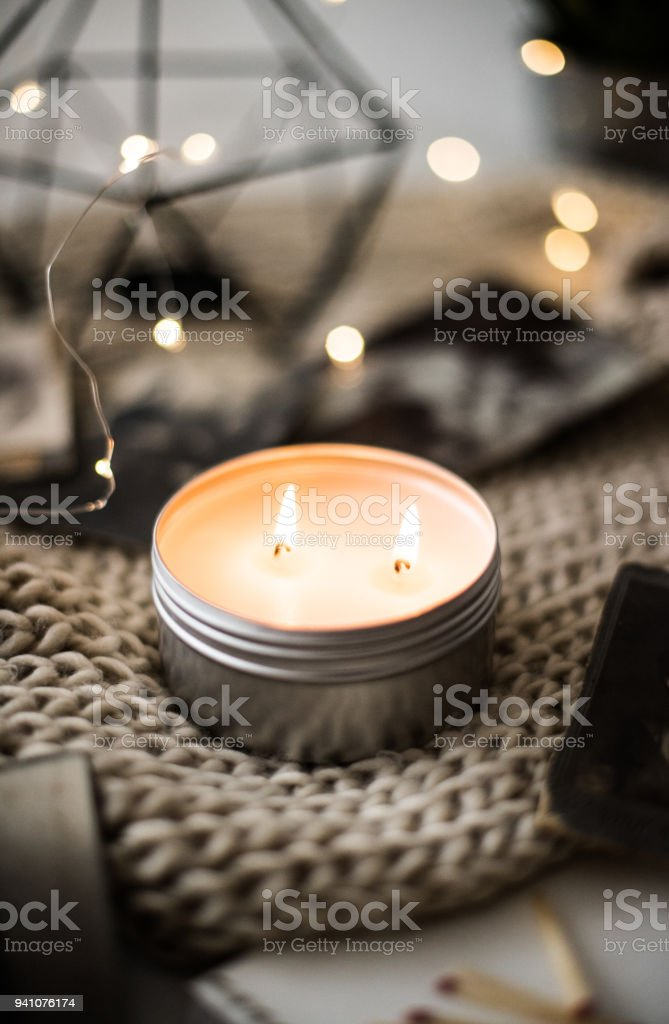 Cozy warm home decoration with burning candle and bokeh lights stock photo