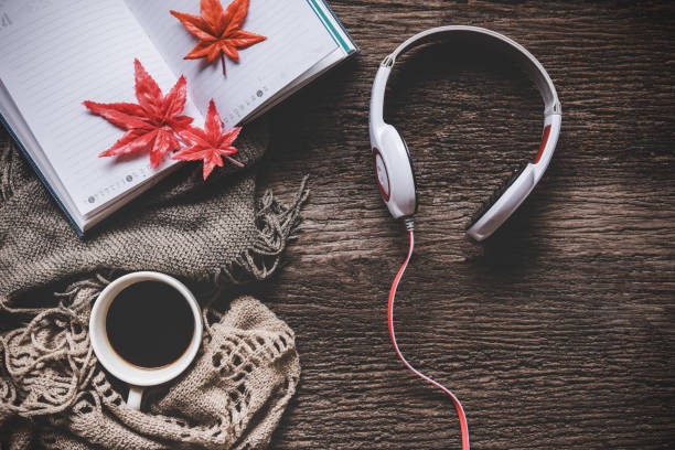 cozy winter background, cup of hot coffee with marshmallow and headphone music and book note, warm knitted sweater, vintage tone. lifestyle and music concept - asian with phone house background stock photos and pictures
