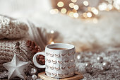 Beautiful Christmas cup with a hot drink on a light blurred background. The concept of home comfort and warmth.