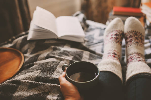 cozy winter day at home with cup of hot tea, book and warm socks. spending weekend in bed, seasonal holidays and hygge concept - hygge imagens e fotografias de stock