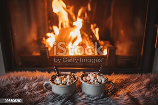 Cups with hot chocolate on fur, fireplace in background