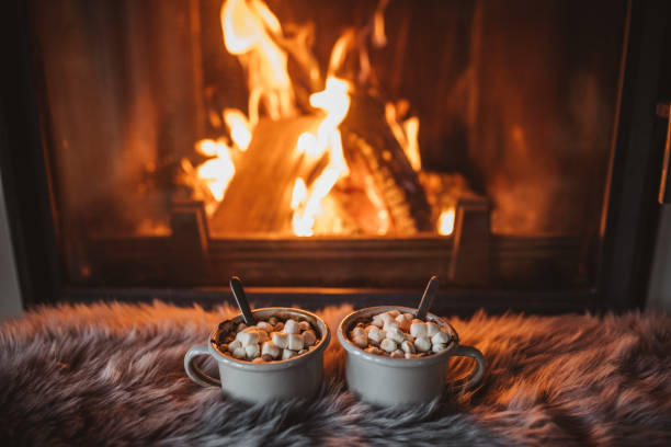 Cozy winter drink Cups with hot chocolate on fur, fireplace in background cozy stock pictures, royalty-free photos & images