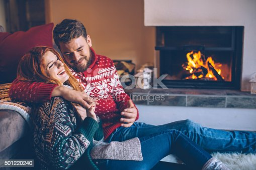 Couple on vacation at mountain cabin. Sitting on the floor on a fur by fireplace in cozy  living room on Christmas. Wearing festive knitted sweaters and socks. Austrian Alps.