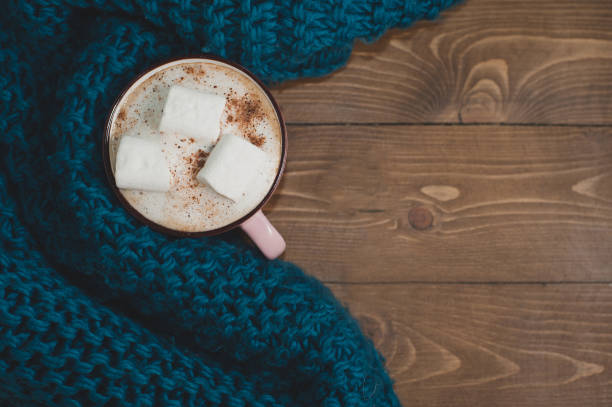 Cozy winter home. A cup of cocoa with marshmallows and a knitted blue scarf on a brown wooden table. Place for text. stock photo